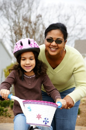 Young girl learning to ride a bike photo