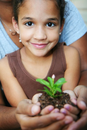 seedling growing: Girl with her mother holding a new flower Stock Photo