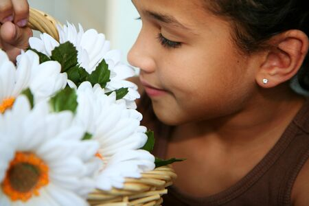 Girl smelling a bunch of white flowers photo