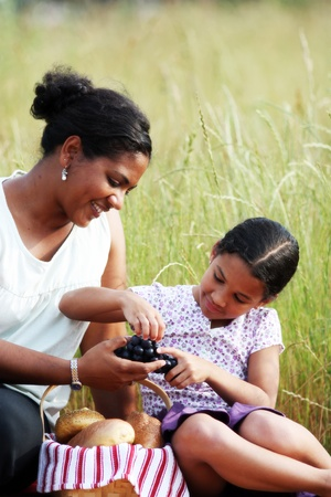 african basket: Mother and Daughter Having A Picnic Lunch Stock Photo