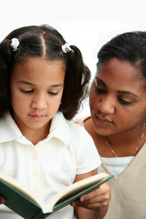 Child reading a book with her teacher photo