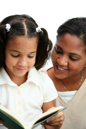 hispanic kids: Child reading a book with her teacher Stock Photo