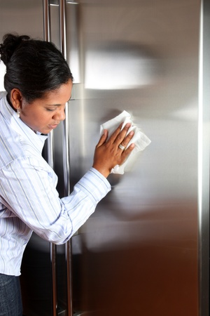 Woman cleaning her stainless steel refrigerator with a cloth photo