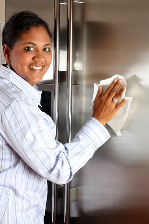 Woman cleaning her stainless steel refrigerator with a cloth Stock Photo - 13164664