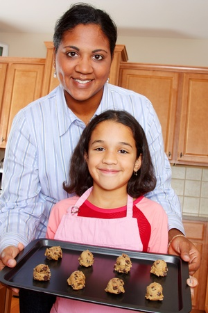 Girl and mother baking chocolate chip cookies in the kitchen photo