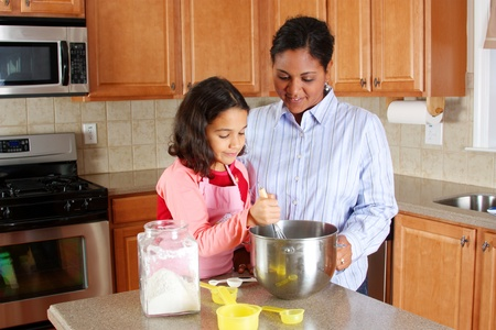 hispanic women: Girl and mother cooking in the kitchen Stock Photo