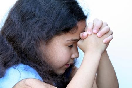 Jong meisje op een witte achtergrond die denkt of bidden Stockfoto
