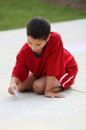 Boy in his driveway playing with chalk photo