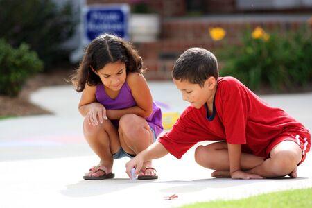 hispanic boy: Los ni�os y ni�as en su camino de entrada a jugar con tiza