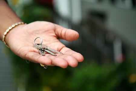 handing: Woman is handing keys to the camera Stock Photo