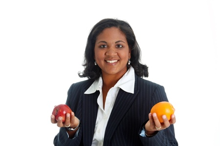 compared: Woman comparing apples and oranges on a white background