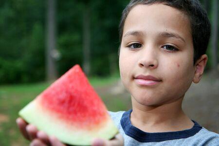8 9 years: Boy eating watermelon in his yard Stock Photo