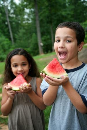 8 9 years: Boyand girl eating watermelon in the yard