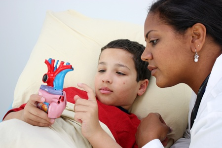 Child laying sick in bed at the hospital with doctor photo