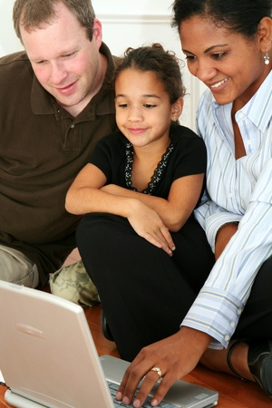 interracial family: Woman and daughter on the computer