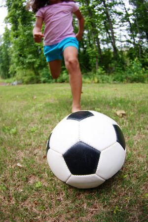 girl kick: Young girl playing soccer in her yard