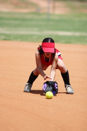 Young girl playing in a softball game