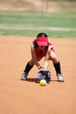 softball: Young girl playing in a softball game