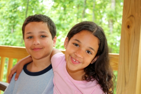 brothers: Brother and Sister sitting together on a deck