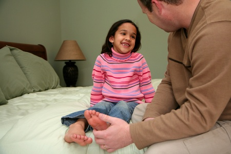 family tickle: Dad tickles his daughter before she goes to bed