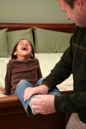 Papa kietelt zijn dochter voordat ze naar bed gaat