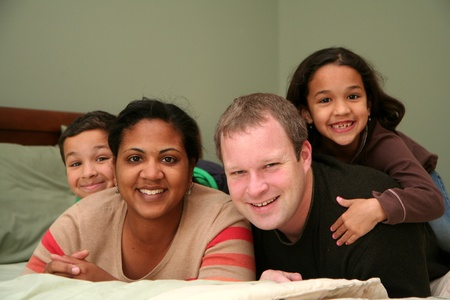 A family laying together on a large bed Stock Photo