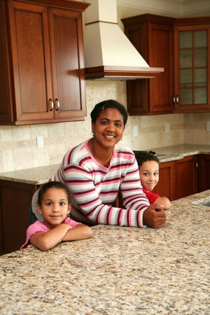 A hispanic family stands in a luxury home kitchen photo
