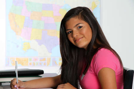 Girl writing at her desk at school Stock Photo - 13293813