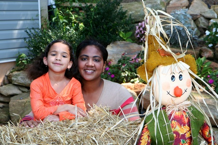 multiple family: A mixed race mother and daughter by a fall display Stock Photo
