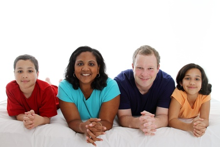 Family laying down together in a bed Stock Photo
