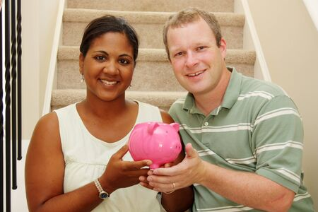 interracial marriage: Couple Holding Piggy Bank With Their Savings