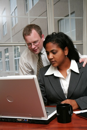Businesswoman working on a computer in an office with coworker photo
