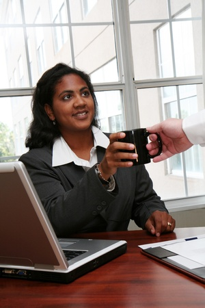 Businesswoman working on a computer and having coffee photo