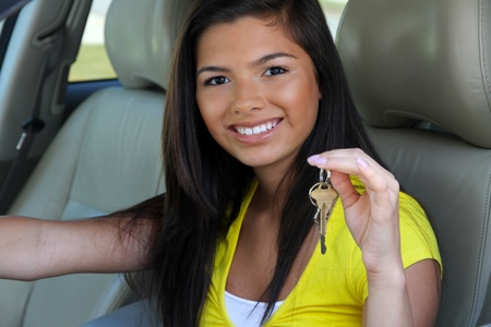 Teen holding up keys to her new car photo
