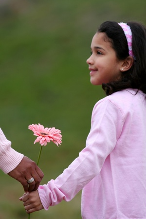 Girl with her mother holding a new flower Stock Photo - 13301664