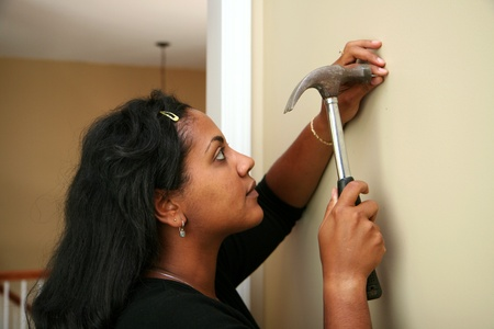 Woman hangs a picture in their new home Stock Photo