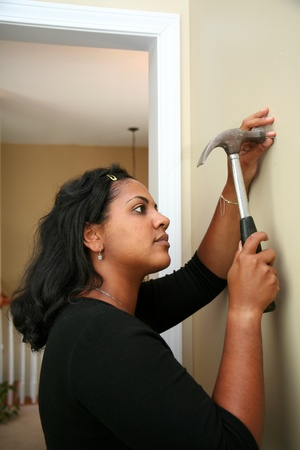 Woman hangs a picture in their new home Stock Photo - 13301509