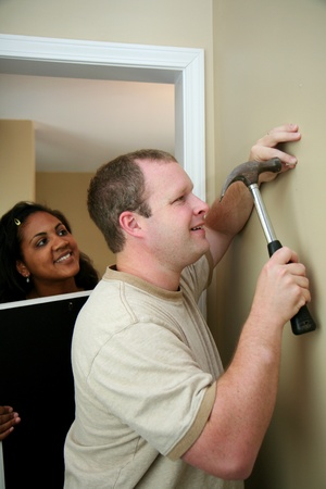 Family hangs a picture in their new home Stock Photo