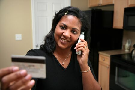 purchase: Woman on the phone using credit card