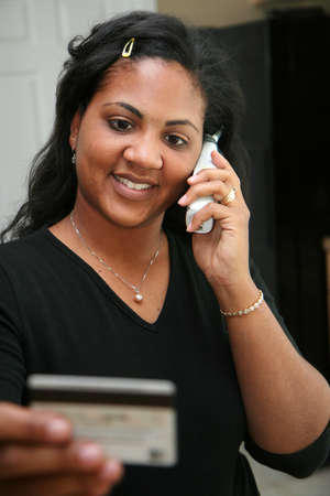 american money: Woman on the phone using credit card