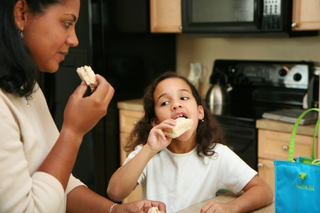 peanut butter and jelly sandwich: Family eating lunch in the kitchen