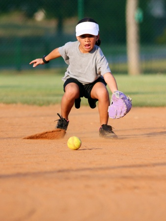 Young girl playing in a game of softball Stock Photo