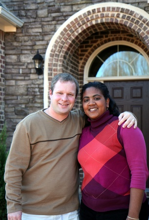 interracial love: Happy couple outside in front of their new house