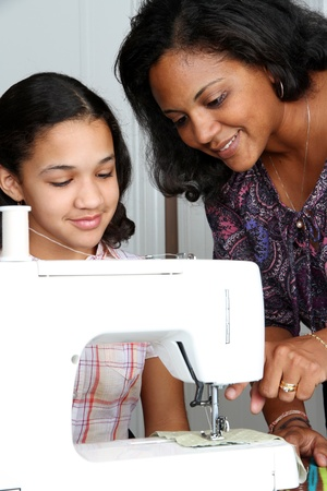 Girl and mother using a sewing machine to make crafts Stock Photo - 13293208