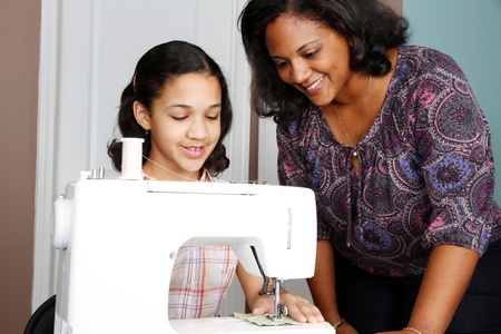 Girl and mother using a sewing machine to make crafts Stockfoto