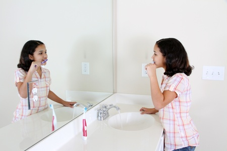 Person looking into a mirror brushing their teeth