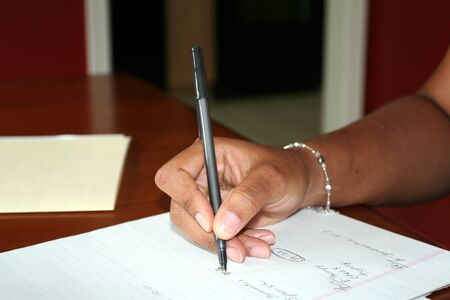note pad and pen: Woman Writing on Pad Stock Photo