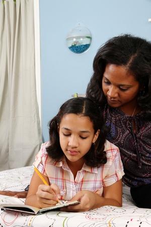madre e hija adolescente: Chica escribiendo en su diario de la cama