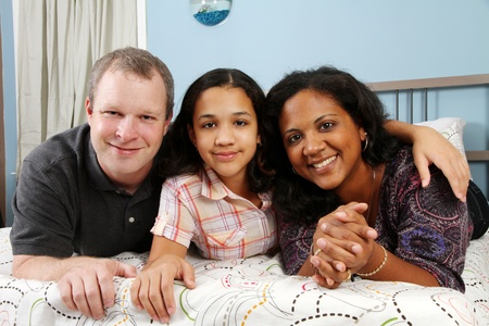 black man white woman: Family laying down together in a bed Stock Photo