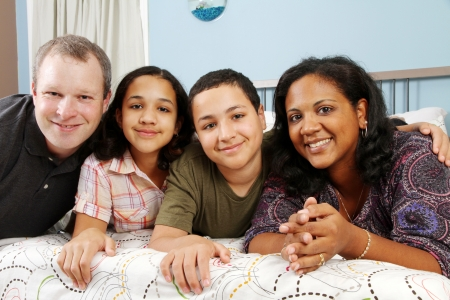 Family laying down together in a bed Foto de archivo